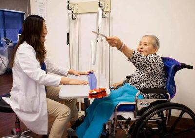 Alcott Rehabilitation therapist with Korean woman in the Rehab gym