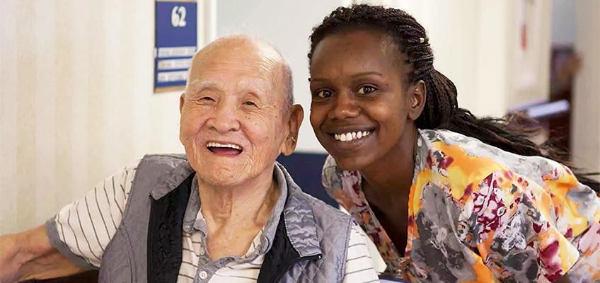 Alcott Rehabilitation nurse smiling with an elderly Korean man