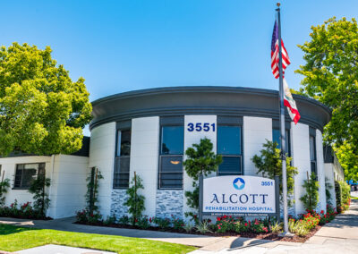 American flag, Lawn, bushes, and sidewalk and sign out front Alcott Rehabilitation