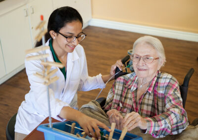 Anaheim Healthcare facility therapist with an elderly woman with dexterity tools in rehab gym