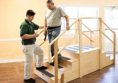 Anaheim Healthcare facility therapist with an elderly man in rehab gym