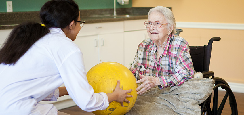 Anaheim Healthcare facility therapist with an elderly woman and a yellow ball in rehab gym