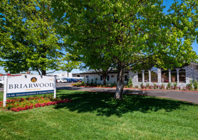 Lawn, flowers, sign, and front of Briarwood Post Acute