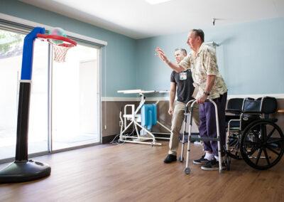 Citrus Nursing Center rehab therapist with an elderly resident shooting baskets