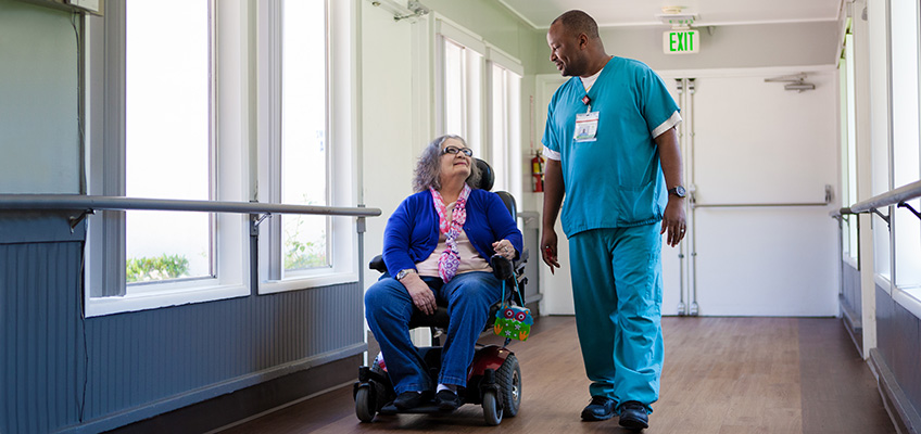 Citrus Nursing Center male nurse with a female elderly resident in a wheelchair
