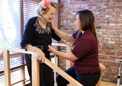 College Vista a rehab therapist and a resident smiling on the steps