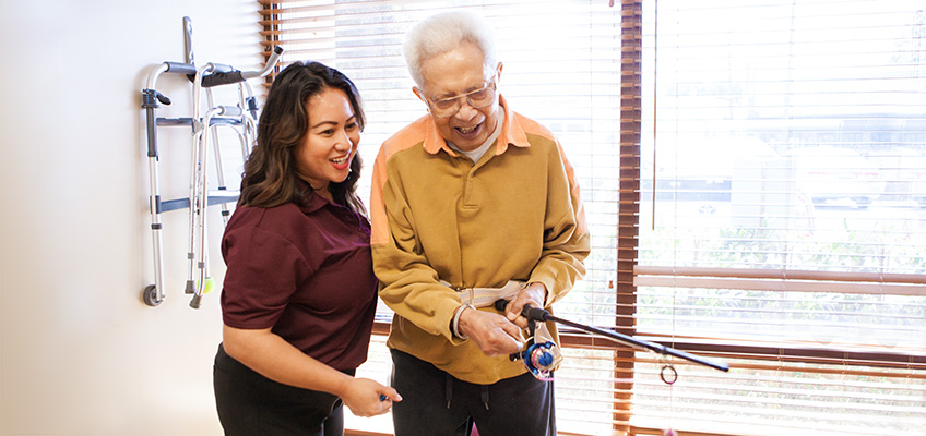 College Vista a occupational therapist and a resident smiling and using a fishing rod