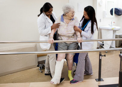 Resident with two rehab therapists in the gym
