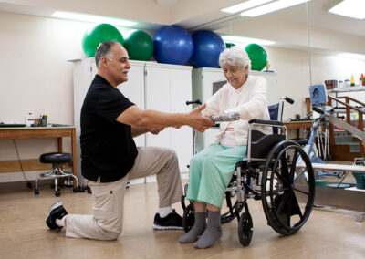 Resident with a rehab therapist in the gym