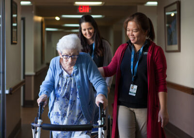 Resident with a nurse in the hallway