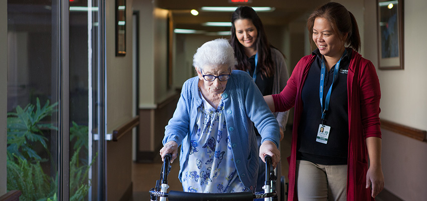 Resident with two nurses in the hallway