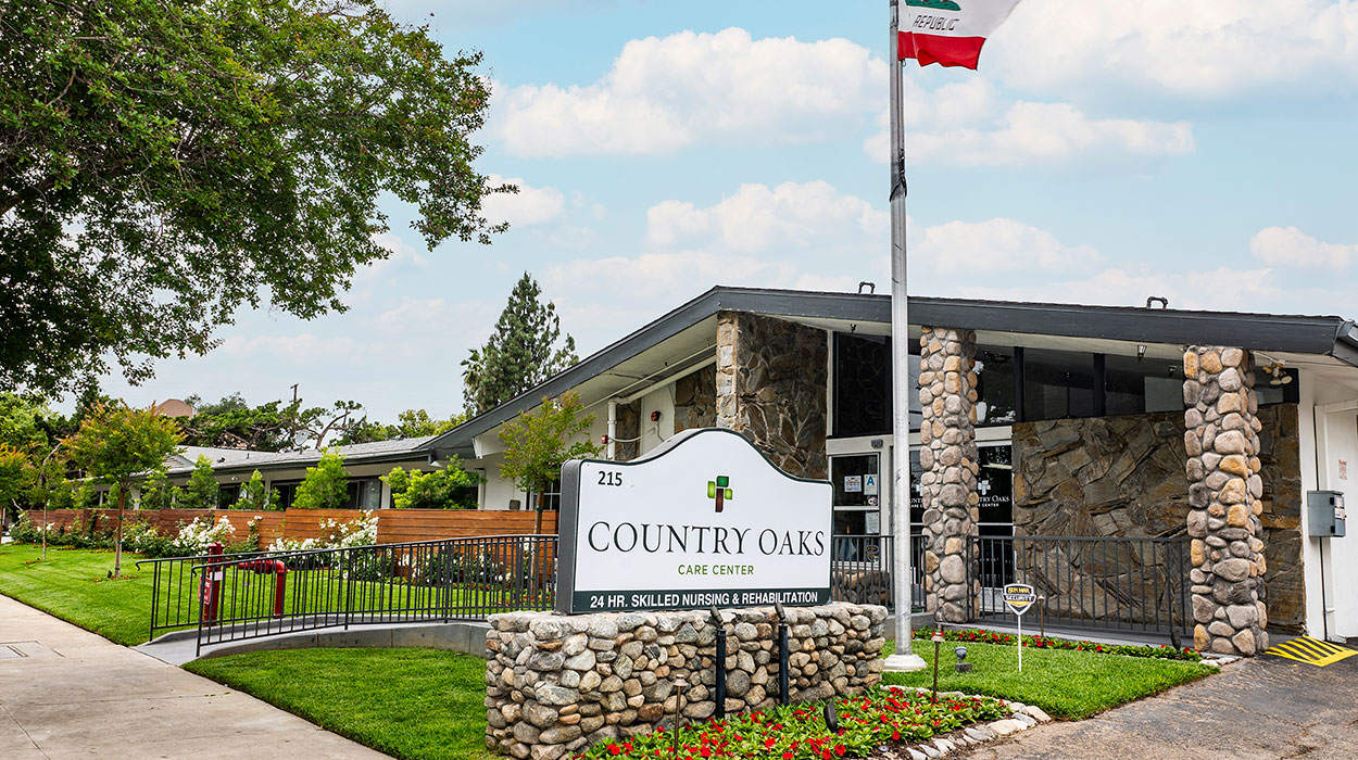 Country Oaks sign and front of facility, flowers and grass