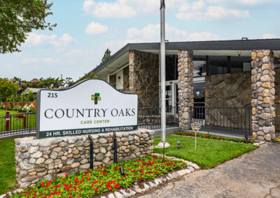 Sign, flowers, front grass and landscaping at Country Oaks care center