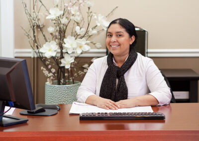 A smiling lady seated at a desk at Country Oaks
