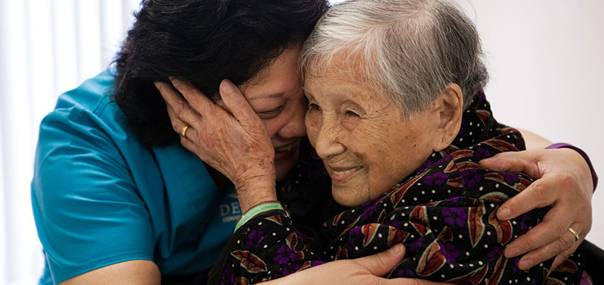 Happy resident and nurse hugging