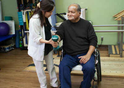 A rehab therapist and a resident in a wheelchair