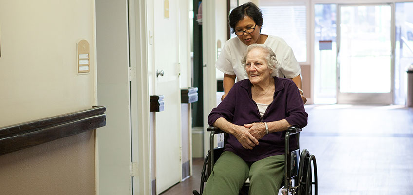 A nurse and a smiling elderly patient in a wheelchair in the hall