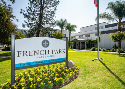 Front of the French Park facility including sign, flowers, trees, and green lawn