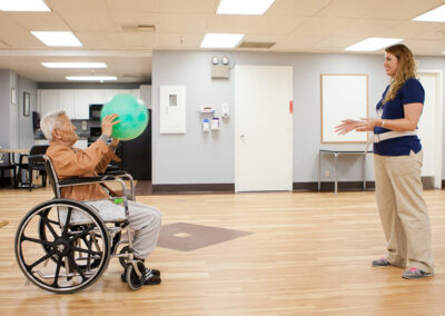 French Park rehab therapist and elderly resident with a ball in a wheelchair