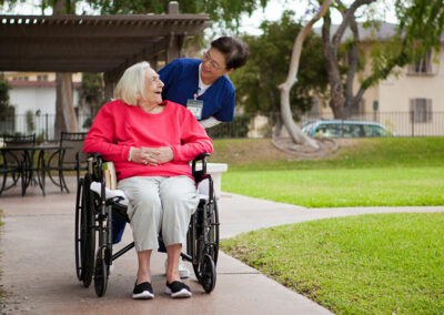 French Park nurse and elderly resident in a wheelchair outside