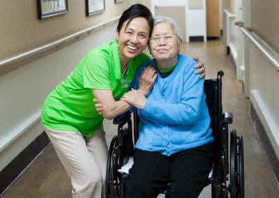 Garden Park nurse and happy elderly resident in a wheelchair