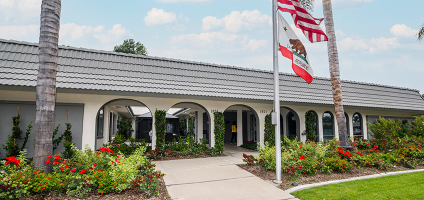 Front of the Gordon Lane facility with a flag pole and green lawn