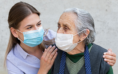 a caregiver and a resident both wearing masks