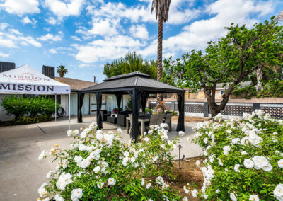shaded outdoor seating, white flowers, and palm trees at Mission Care Center