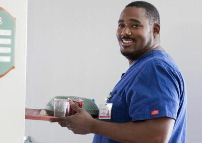smiling caregiver serving a meal at Mission Care Center