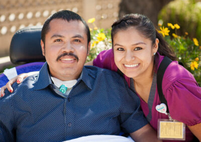 smiling staff member with a resident outside at Mission Care Center