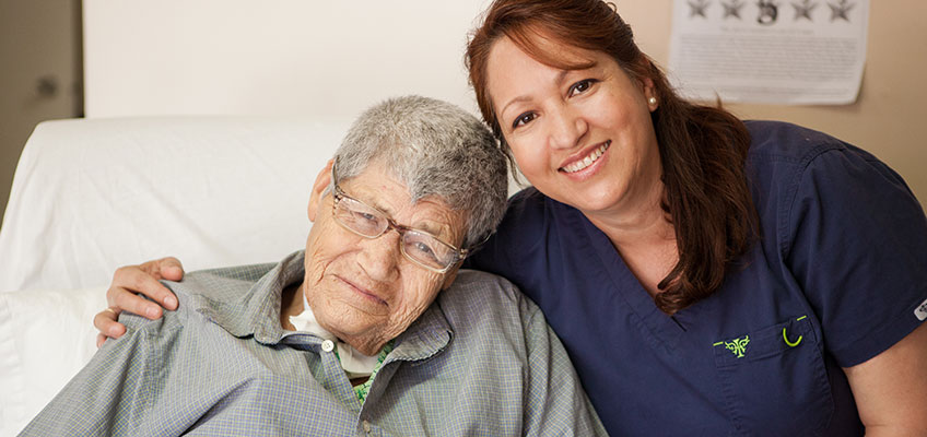 smiling staff member with a resident at Mission Care Center