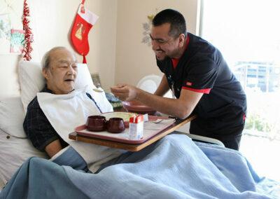 Monterey Park staff member helping an elderly resident eat a meal