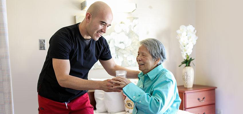 Monterey Park nurse helping an elderly resident take meds