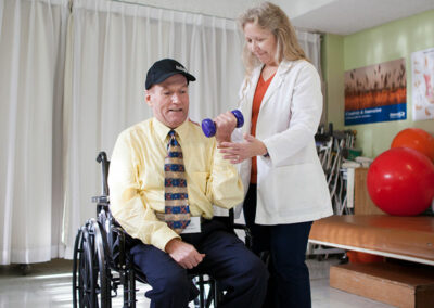 North Valley Nursing Center rehab therapist and a resident using weights