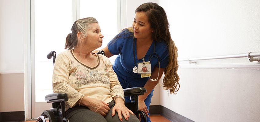 North Valley Nursing Center nurse with a resident in a wheelchair