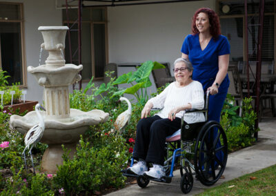 Pacific Post-Acute caregiver pushing a resident in a wheelchair both happy
