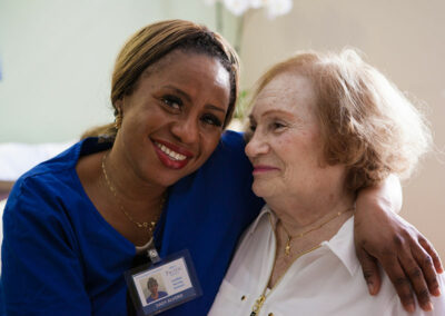 A female nurse with an elderly resident both smiling at Pacific Post-Acute