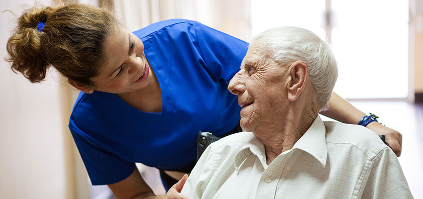 Pacific Post-Acute nurse in the hallway with a resident