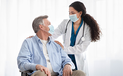 Doctor with an elderly resident in a wheelchair both wearing masks