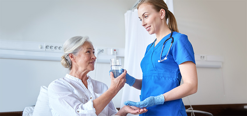 Nurse leaning down to speak with a patient