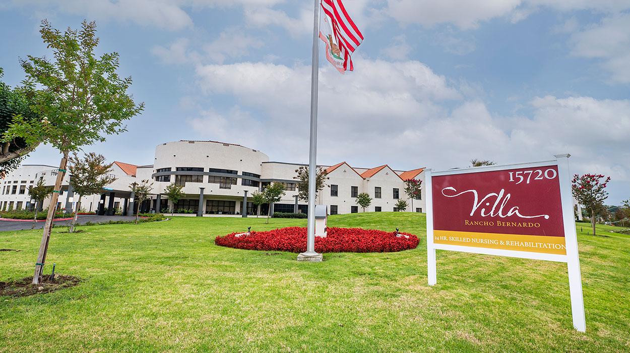 front of Villa Rancho Bernardo with sign, flags and green grass